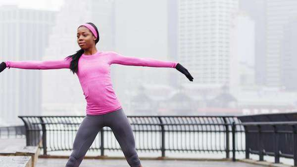 A woman does yoga poses before a run in the rain, in Brooklyn Royalty-free stock video