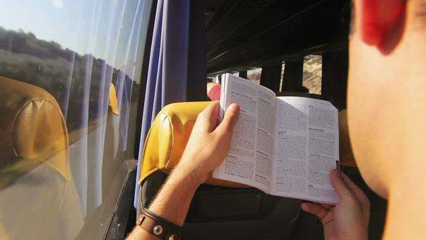 Over the shoulder shot of a young man reading a book as he takes a bus ride Royalty-free stock video
