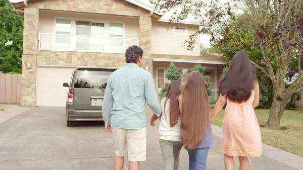 A family walks up their driveway and back into their house Royalty-free stock video