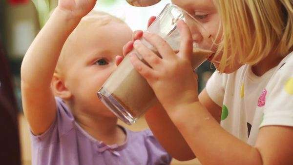 Two young sisters drink chocolate milk Royalty-free stock video