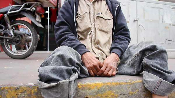 A homeless man sits on the curb in a small town in Mexico Royalty-free stock video