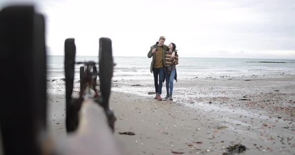 Young couple walking on a beach in winter Royalty-free stock video