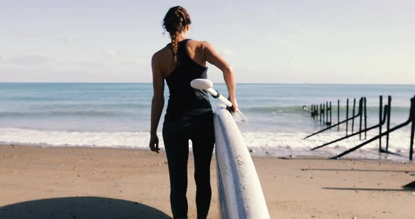 Female walking with paddle board towards the sea Royalty-free stock video