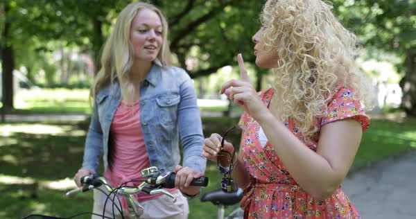 Young female friends walking through a park together with a bicycle Royalty-free stock video