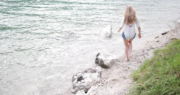 Young adult woman walking barefoot in lake Royalty-free stock video