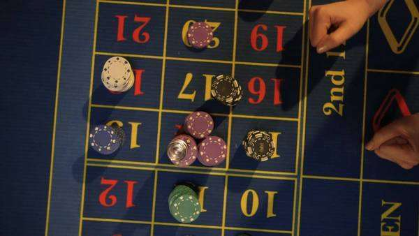 Birdseye close-up Player claims her winnings from the Roulette Table Royalty-free stock video