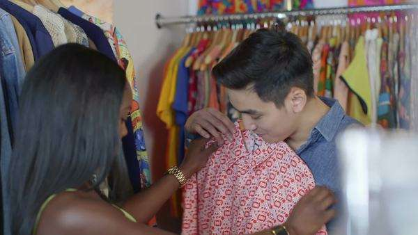 Medium close-up of A Young Woman and a young Man browse through a shop of colorful vintage clothing Royalty-free stock video