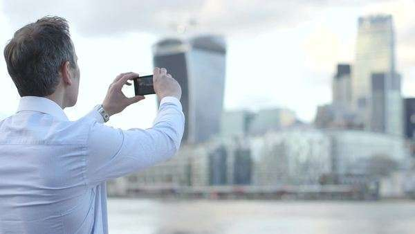 Business man takes a photo of the city scape and River Thames with his smart phone Royalty-free stock video