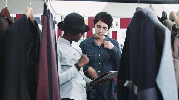 Fashion designers looking at digital tablet and clothes in studio Royalty-free stock video