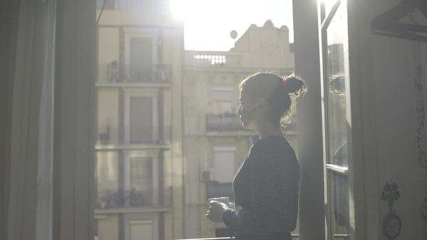 Young woman enjoying sunshine and drink on balcony in Barcelona Royalty-free stock video