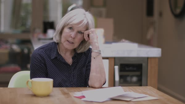 Senior adult woman opening bills at home on kitchen table Royalty-free stock video