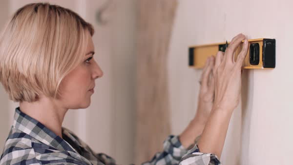 Adult woman with spirit level measuring wall in new home Royalty-free stock video