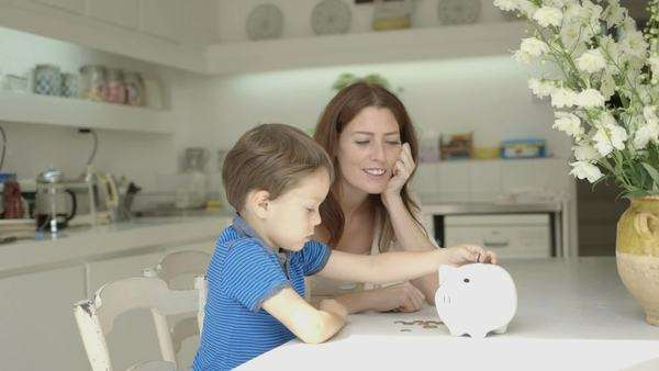 Mother helping son to save money in piggy bank Royalty-free stock video