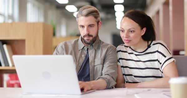 Coworkers looking at a laptop together Royalty-free stock video