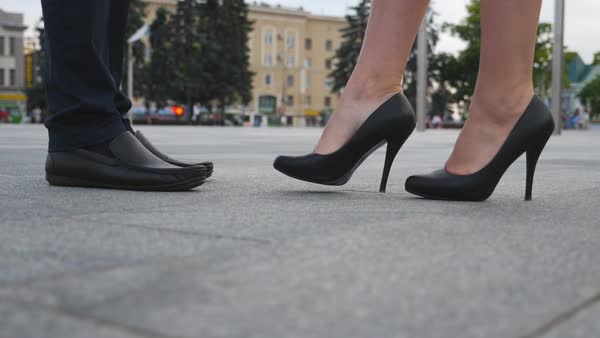 0187a5eb982 Feet of businessman in black shoes and businesswoman on high heels standing  at city street. stock footage