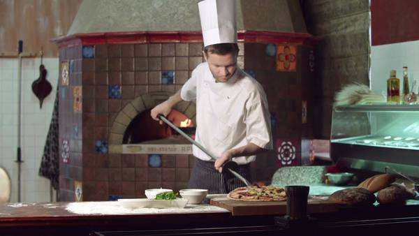 Static shot of restaurant cook taking pizza with shovel out of the stove Royalty-free stock video