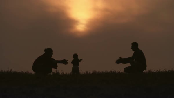 Silhouettes of mother and father teaching their baby how to walk Royalty-free stock video
