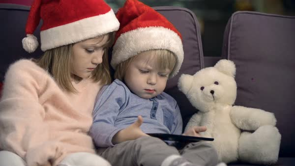 Cute kids in Santa hats sitting together on sofa and watching Christmas movie on tablet  Royalty-free stock video