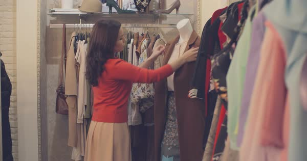 Shop assistant dressing mannequin and checking if everything is good on racks Royalty-free stock video