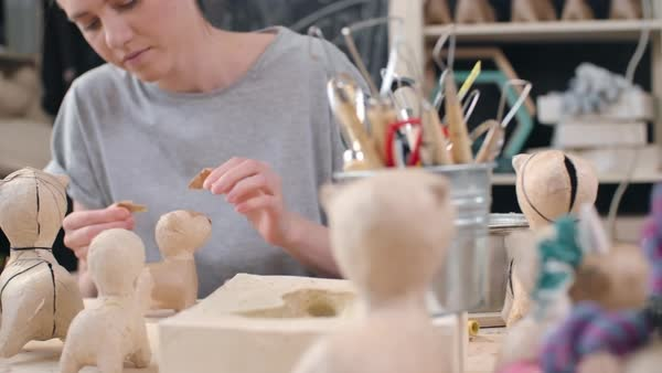 Tracking shot of young female artist making papier-mache dog figures of craft paper Royalty-free stock video