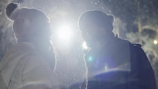 Happy couple laughing and kissing in the street light at snowy winter night  Royalty-free stock video