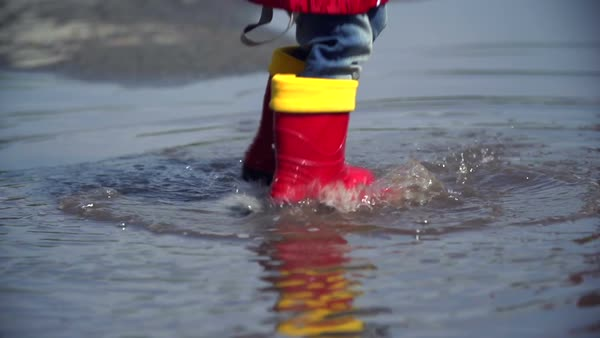 Close up of a young child's rubber boots bouncing in puddle Royalty-free stock video