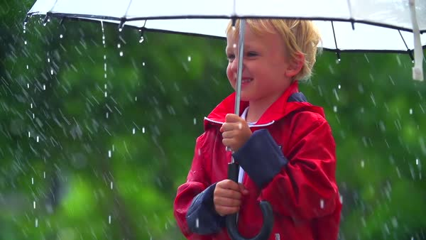 Close up of little boy standing under an umbrella in the rain Royalty-free stock video