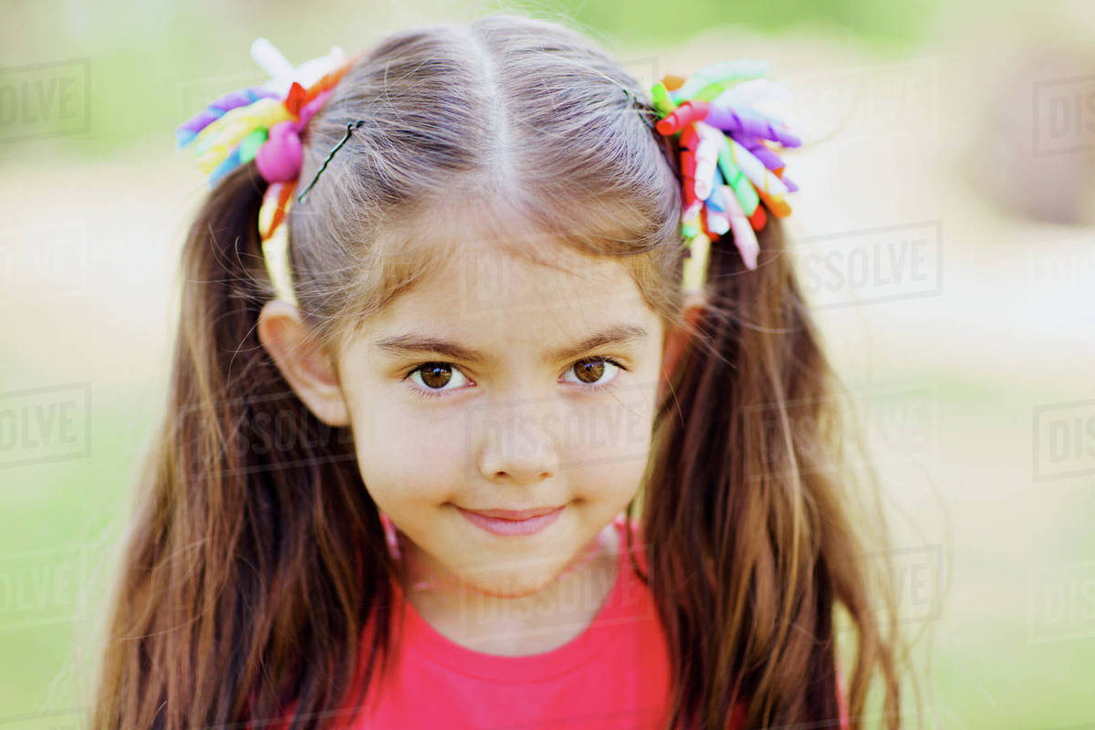 portrait of cute little girl with two ponytails outdoors stock