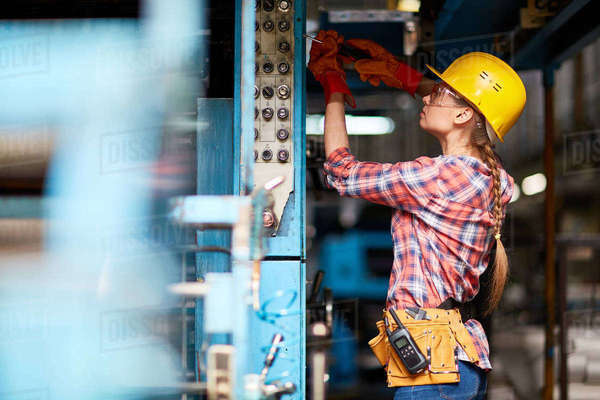 female electrician technician inspecting a young trainee at factory stock photo