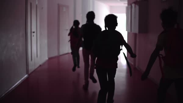 Four friends trying to outrun each other in school corridor in slow motion Royalty-free stock video