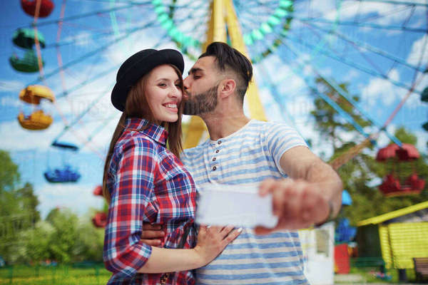 Guy kissing his girlfriend while making selfie Royalty-free stock photo