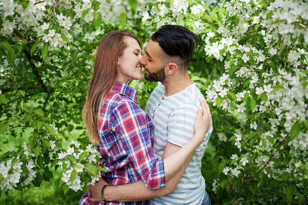 Happy amorous couple embracing in blooming garden Royalty-free stock photo
