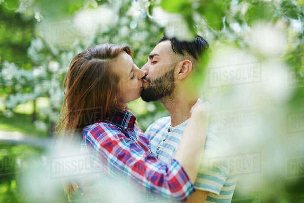Amorous young woman and guy kissing in park Royalty-free stock photo