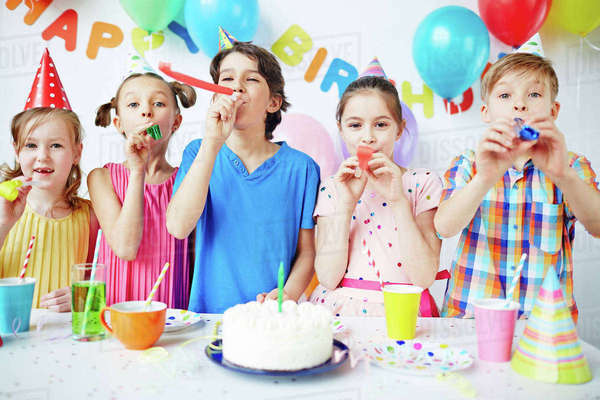 Row of happy kids blowing horns at birthday party Royalty-free stock photo