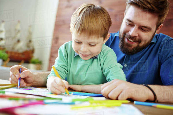 Cute Boy And His Father Coloring Pictures With Crayons Royalty Free Stock Photo