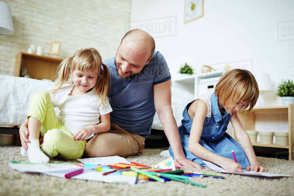 Young man and his daughters drawing at home Royalty-free stock photo