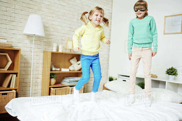 Little girls jumping on bed at home Royalty-free stock photo
