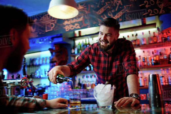 Bartender flirting with customer while pouring him whiskey in bar Royalty-free stock photo