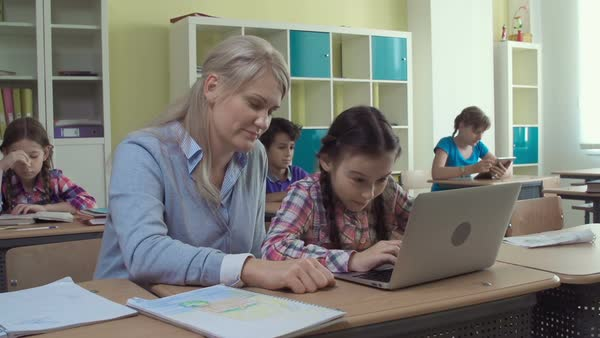 Teacher helping pupil with laptop handling at informatics lesson Royalty-free stock video