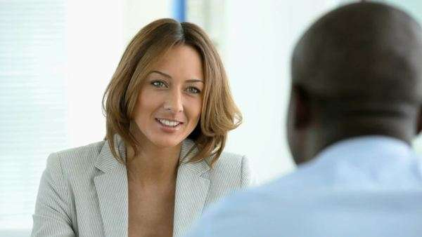 African-American man seen from his back taking part in a job interview or other business meeting talking to a smiling lady Royalty-free stock video