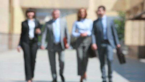 Elegant business group of four walking out of focus, good for business backgrounds and presentations Royalty-free stock video