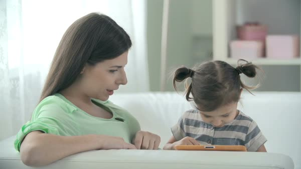Mother and daughter sitting on the sofa and playing with digital device Royalty-free stock video