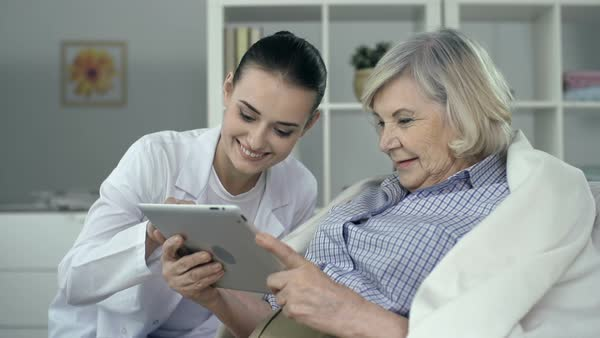 Close up of senior woman wrapped in plaid using digital tab assisted by young nurse Royalty-free stock video