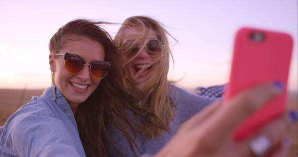 Beautiful girl friends taking selfies on road trip at sunset with vintage car Royalty-free stock video
