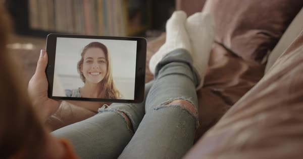 Happy Woman having video chat waving hello to friend on vacation at home through internet using digital tablet app on sofa sharing connected lifestyle faded denim jeans Royalty-free stock video