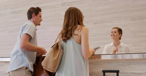 Attractive happy couple arriving at hotel reception lobby travelling on vacation checking in carrying luggage on honeymoon using payment device Royalty-free stock video
