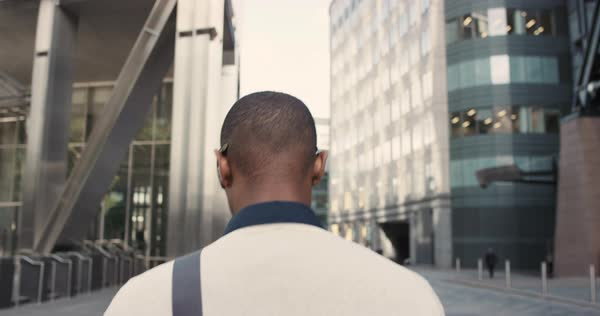 Rear view businessman walking in city commuting independently between glass buidlings Royalty-free stock video