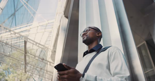 Man using business app on smart phone walking in city. Handsome young businessman communicating on smartphone smiling confident. Urban black male professional commuting in his 20s Royalty-free stock video