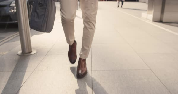 Close-up crop of businessman feet walking in city. Man commuting to work. Steadicam shot in slow motion with warm natural light on sidewalk Royalty-free stock video