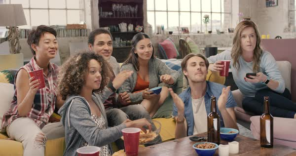 Happy diverse group of student sports fans throwing arms up in excitement celebrating goal watching sports event on TV together bonding as friends eating snacks drinking beer Royalty-free stock video